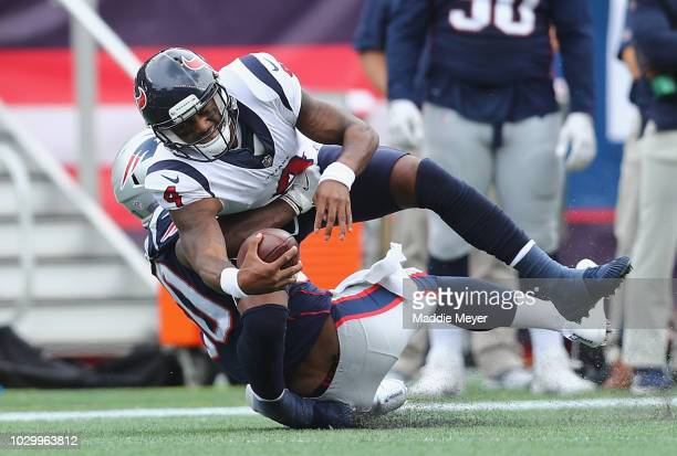 Nicholas Grigsby of the New England Patriots tackles Deshaun Watson of the Houston Texans during the first half at Gillette Stadium on September 9...