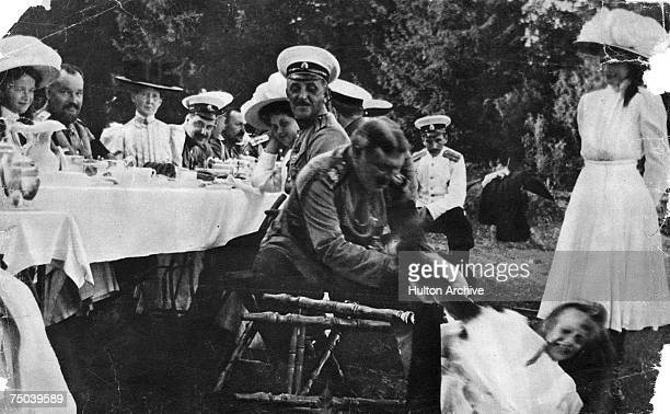 Nicholas II the last Tsar of Russia helping one of his daughters up from a fallen chair during an outdoor family dinner circa 1910