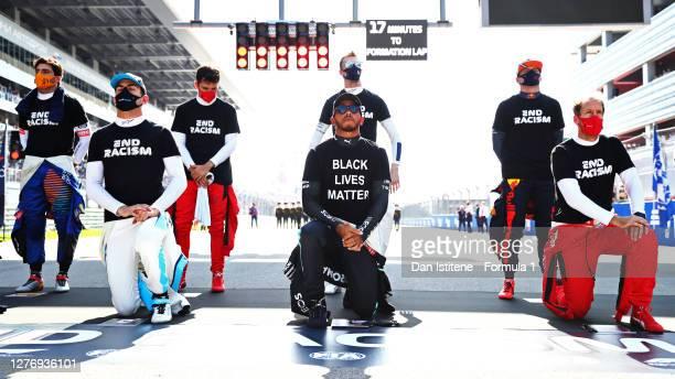 Nicholas Latifi of Canada and Williams, Lewis Hamilton of Great Britain and Mercedes GP, and Sebastian Vettel of Germany and Ferrari kneel as Max...