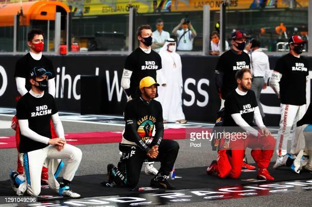 Nicholas Latifi of Canada and Williams, Lewis Hamilton of Great Britain and Mercedes GP, and Sebastian Vettel of Germany and Ferrari kneel as Kimi...