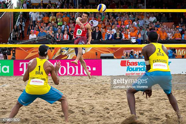 Nicholas Lucena from the United States attacks Pedro Solberg from Brazil and his teammate Evandro Goncalves Oliveira Junior during the FIVB Beach...