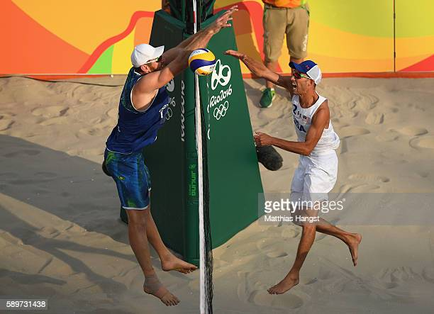 Nicholas Lucena of United States spikes over Alison Cerutti of Brazil during the Men's Beach Volleyball Quarterfinal match between the United States...