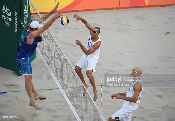 Nicholas Lucena of United States spikes the ball against Alison Cerutti of Brazil during the Men's Beach Volleyball Quarterfinal match between the...