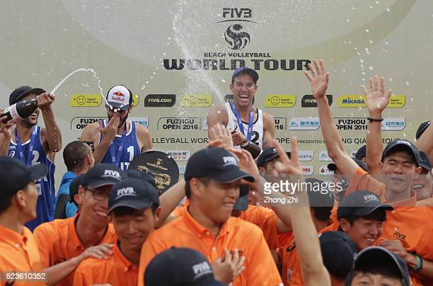 Nicholas Lucena of USA celebrate with volunteers with champagne during the Award Ceremony during the FIVB Beach Volleyball World Tour Fuzhou Open on...