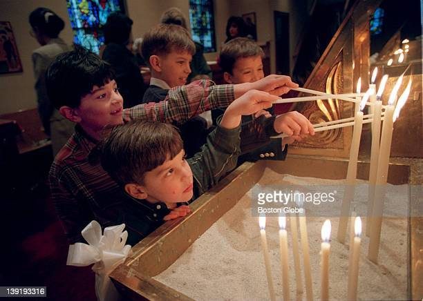 Nicholas Malatos and his older brother James light candles during Orthodox Easter services at the Greek Orthodox Cathedral of New England in Boston...