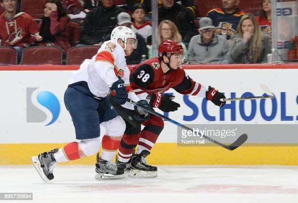 Nicholas Merkley of the Arizona Coyotes and Connor Brickley of the Florida Panthers skate for the puck during the first period at Gila River Arena on...