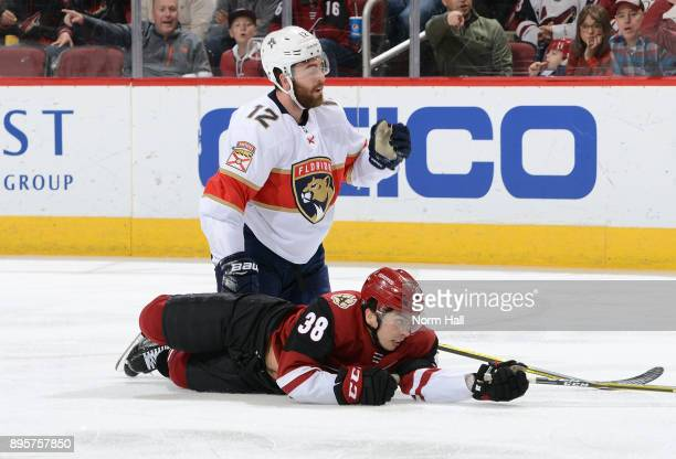 Nicholas Merkley of the Arizona Coyotes and Ian McCoshen of the Florida Panthers look for the puck after colliding during the third period at Gila...