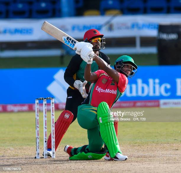 Nicholas Pooran of Guyana Amazon Warriors hits 6 and Denesh Ramdin of St Kitts & Nevis Patriots watch during the Hero Caribbean Premier League match...