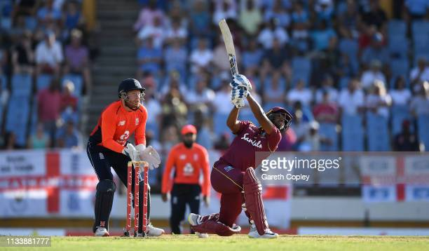 Nicholas Pooran of the West Indies hits out for six runs watched by England wicketkeeper Jonathan Bairstow during the First Twenty20 International...