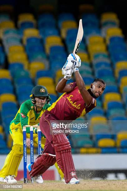 Nicholas Pooran of West Indies hits 6 and Alex Carey of Australia watch during the 2nd ODI between West Indies and Australia at Kensington Oval,...