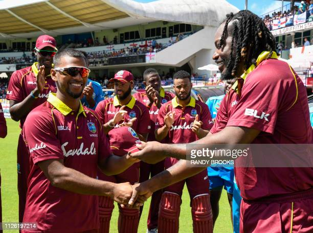 Nicholas Pooran receives his cap from Chris Gayle of West Indies on debut for the 1st ODI between West Indies and England at Kensington Oval...