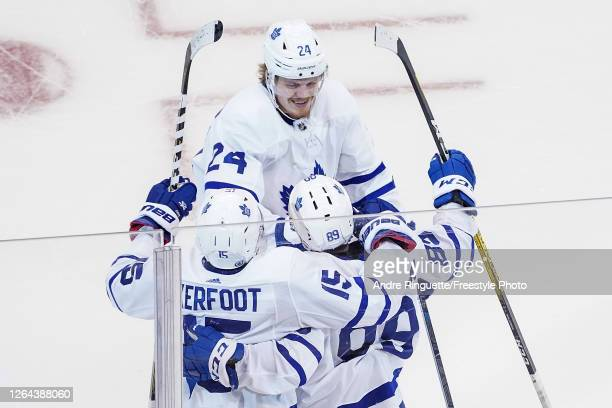 Nicholas Robertson of the Toronto Maple Leafs is congratulated by his teammates Kasperi Kapanen and Alexander Kerfoot after scoring his first career...