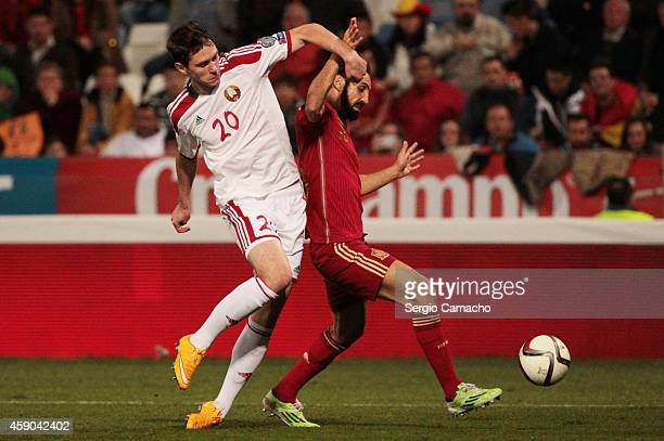 Nicholas Signevich of Belarus duels for the ball with Juan Francisco Torres of Spain during the UEFA EURO 2016 Group C Qualifier football match...