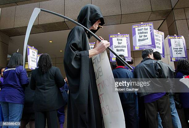 Nicholas Walsh dressed as the Grim Reaper paces near dozens of protestors demonstrate outside the Ronald Reagan Building before a meeting discussing...
