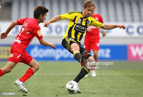 Nicholas Ward of the Wellington Phoenix controls the ball watched by Zenon Caravella of Adelaide United during the round seven A-League match between...