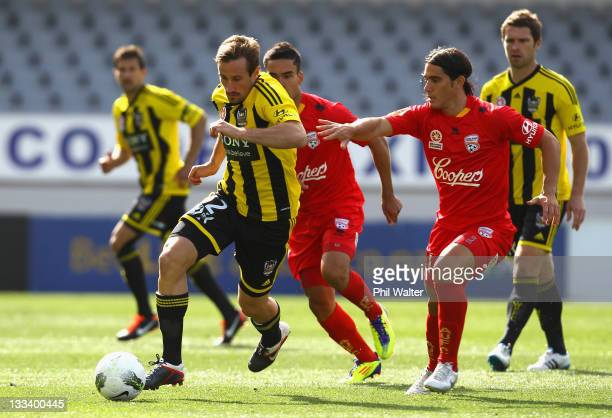 Nicholas Ward of the Wellington Phoenix is challenged by Francisco Usucar of Adelaide United during the round seven A-League match between the...