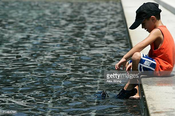 Nicholas Wood of Rockville, Maryland, cools himself off by the fountain as he visits the World War II Memorial July 17, 2006 in Washington, DC. The...