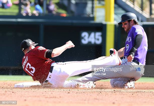 Nick Ahmed of the Arizona Diamondbacks attempts to tag out a stealing Mike Tauchman of the Colorado Rockies during the third inning of a spring...