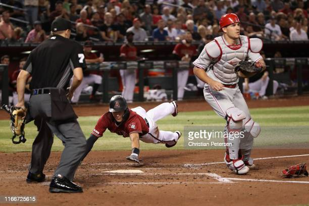 Nick Ahmed of the Arizona Diamondbacks dives into home plate to score a run past catcher JT Realmuto of the Philadelphia Phillies during the fourth...