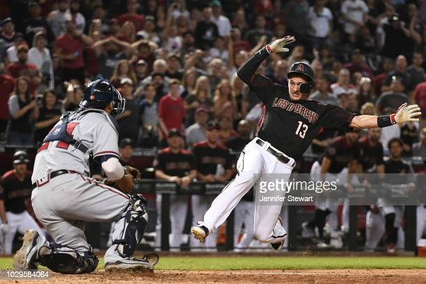 Nick Ahmed of the Arizona Diamondbacks is out at home by Kurt Suzuki of the Atlanta Braves in the tenth inning of the MLB game at Chase Field on...