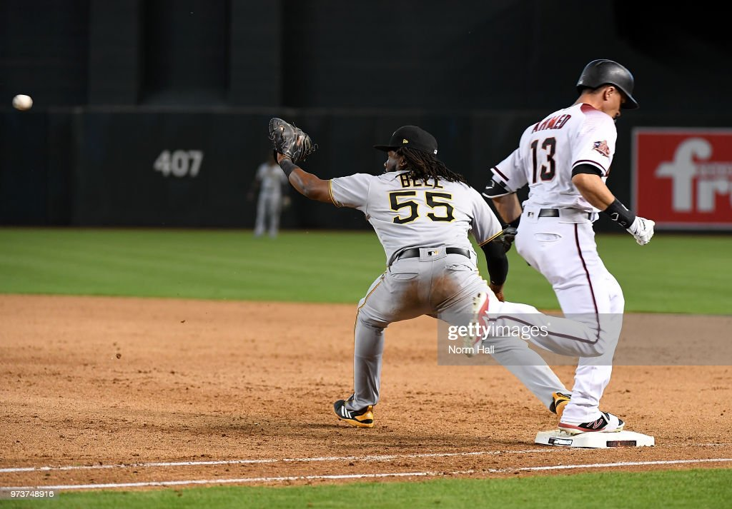 Nick Ahmed #13 of the Arizona Diamondbacks is safe at first base as Josh Bell #55 of the Pittsburgh Pirates stretches for the ball during the ninth inning at Chase Field on June 13, 2018 in Phoenix, Arizona. Pirates won 5-4.