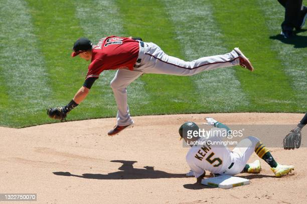 Nick Ahmed of the Arizona Diamondbacks jumps over Tony Kemp of the Oakland Athletics after getting him out at second base and turning a double play...