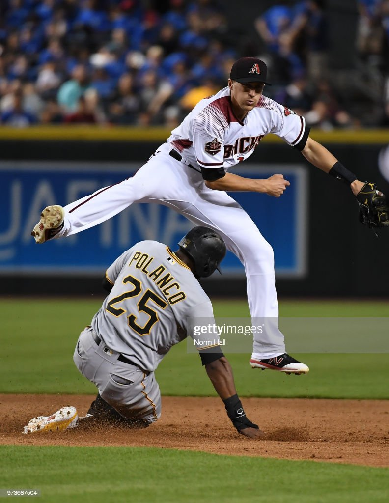 Nick Ahmed #13 of the Arizona Diamondbacks makes a leaping double play over the top of Gregory Polanco #25 of the Pittsburgh Pirates during the sixth inning at Chase Field on June 13, 2018 in Phoenix, Arizona.