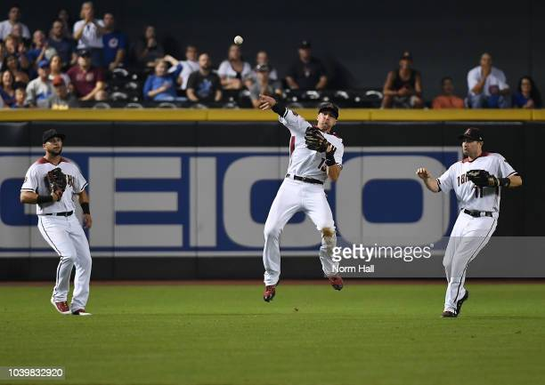 Nick Ahmed of the Arizona Diamondbacks makes an off balance throw as teammates David Peralta and AJ Pollock look on during a game against the Chicago...