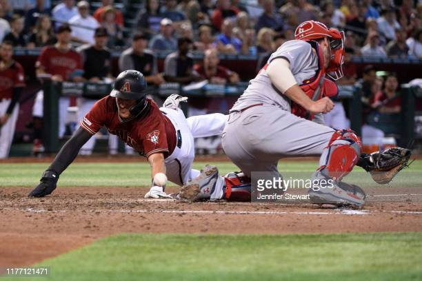 Nick Ahmed of the Arizona Diamondbacks safely slides home against Matt Wieters of the St. Louis Cardinals in the sixth inning of the MLB game at...