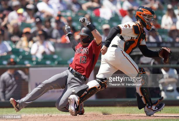 Nick Ahmed of the Arizona Diamondbacks scores ahead of the throw to catcher Buster Posey of the San Francisco Giants in the top of the fifth inning...