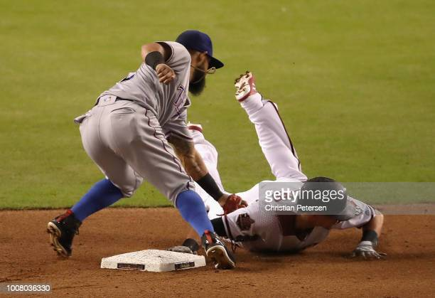Nick Ahmed of the Arizona Diamondbacks slides back into second base ahead of infielder Rougned Odor of the Texas Rangers during the fourth inning of...