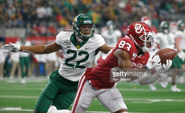 Nick Basquine of the Oklahoma Sooners makes a touchdown catch in front of JT Woods of the Baylor Bears in the third quarter of the Big 12 Football...