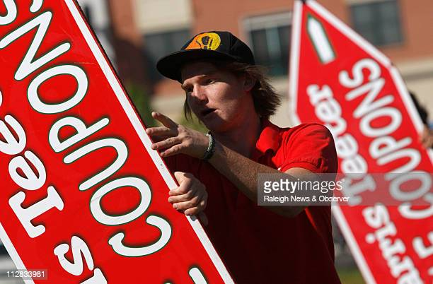 Nick Baxter of Raleigh rotates a sign as AArow Advertising's sign spinners have a weekly practice session at North Hills East in Raleigh North...
