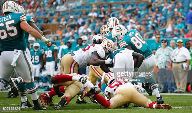 Nick Bellore and Ahmad Brooks of the San Francisco 49ers tackle Jay Ajayi of the Miami Dolphins during the game at Hard Rock Stadium on November 27,...
