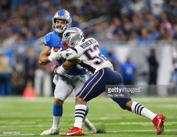 Nick Bellore of the Detroit Lions runs the ball and tackled by Elandon Roberts of the New England Patriots in the second half at Ford Field on...