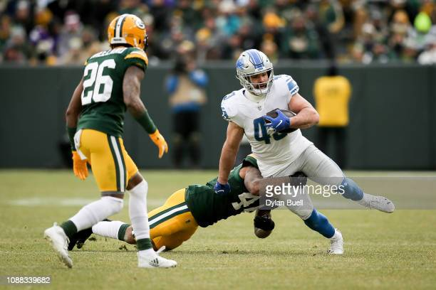 Nick Bellore of the Detroit Lions runs with the ball while being tackled by Antonio Morrison in the third quarter at Lambeau Field on December 30...