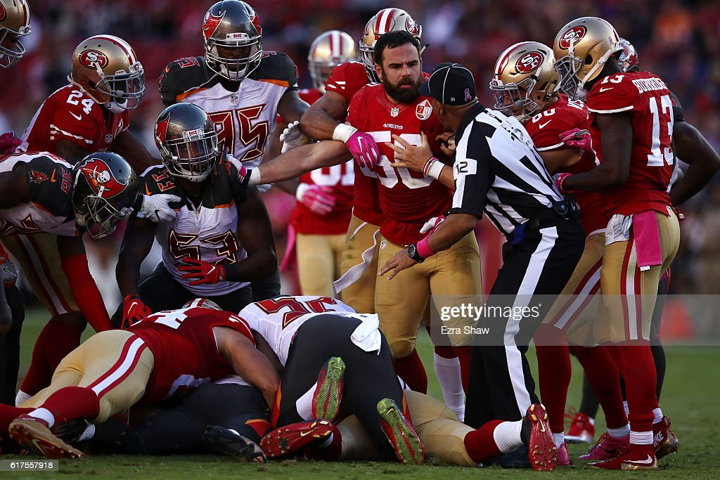Nick Bellore #50 of the San Francisco 49ers is held back after a scrum on the field against the Tampa Bay Buccaneers during their NFL game at Levi's Stadium on October 23, 2016 in Santa Clara, California.