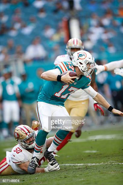 Nick Bellore of the San Francisco 49ers trips up Ryan Tannehill of the Miami Dolphins during the game at Hard Rock Stadium on November 27, 2016 in...