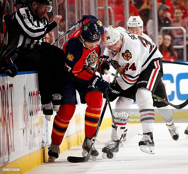 Nick Bjugstad of the Florida Panthers digs the puck out from the boards against Jiri Sekac of the Chicago Blackhawks at the BBT Center on January 22...