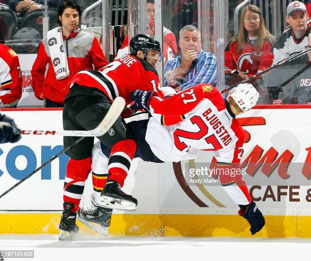 Nick Bjugstad of the Florida Panthers is checked off his feet by Adam Henrique of the New Jersey Devils during the game at the Prudential Center on...