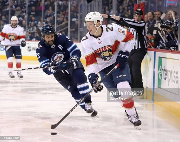 Nick Bjugstad of the Florida Panthers plays the puck away from Dustin Byfuglien of the Winnipeg Jets during third period action at the Bell MTS Place...