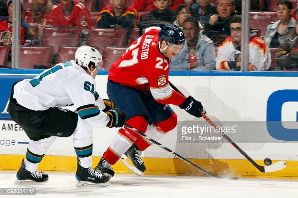 Nick Bjugstad of the Florida Panthers skates with the puck against Justin Braun of the San Jose Sharks at the BBT Center on January 21 2019 in...