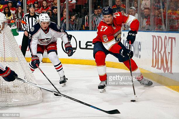 Nick Bjugstad of the Florida Panthers skates with the puck against Markus Nutivaara of the Columbus Blue Jackets at the BBT Center on November 26...