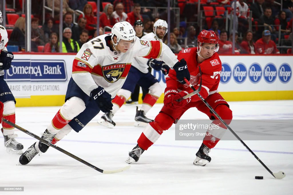 Nick Bjugstad #27 of the Florida Panthers tries to skate past the stick of Dylan Larkin #71 of the Detroit Red Wings at Little Caesars Arena on December 11, 2017 in Detroit, Michigan. Florida won the game 2-1 in overtime.