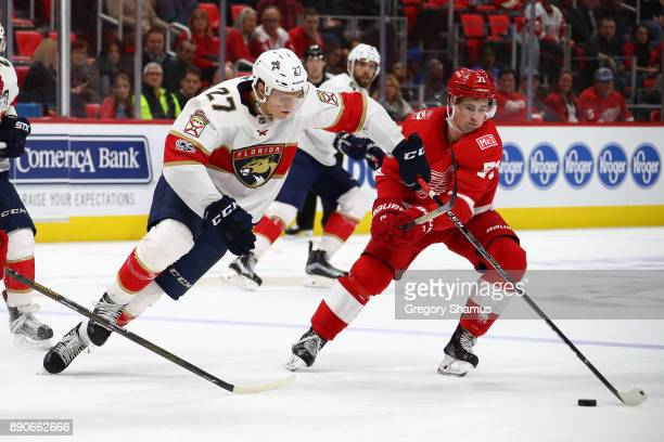 Nick Bjugstad of the Florida Panthers tries to skate past the stick of Dylan Larkin of the Detroit Red Wings at Little Caesars Arena on December 11...