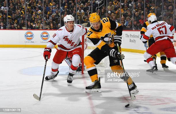 Nick Bjugstad of the Pittsburgh Penguins handles the puck against Jake Gardiner of the Carolina Hurricanes at PPG PAINTS Arena on March 8, 2020 in...