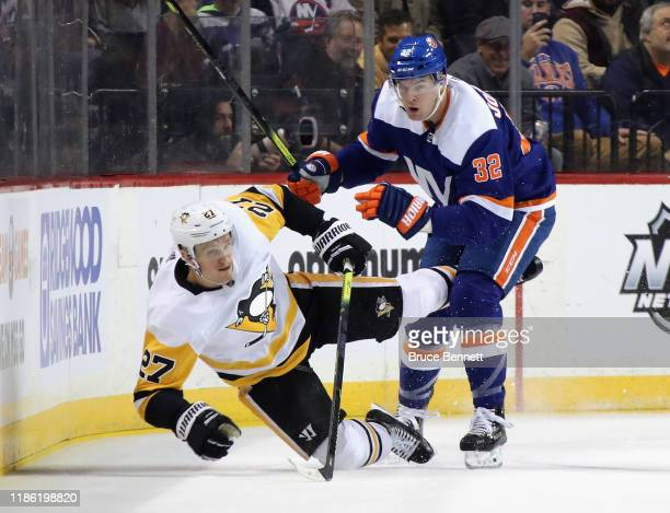 Nick Bjugstad of the Pittsburgh Penguins is checked by Ross Johnston of the New York Islanders during the first period at the Barclays Center on...