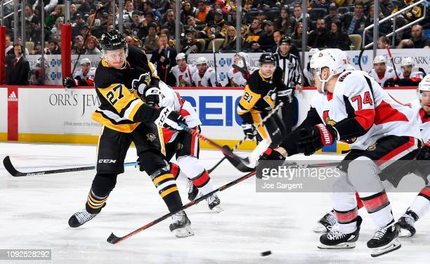 Nick Bjugstad of the Pittsburgh Penguins shoots against Mark Borowiecki of the Ottawa Senators at PPG Paints Arena on February 1 2019 in Pittsburgh...