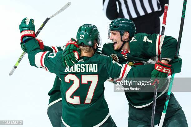 Nick Bonino and Nico Sturm of the Minnesota Wild celebrate after Nick Bjugstad scores a goal during the third period against the Vegas Golden Knights...