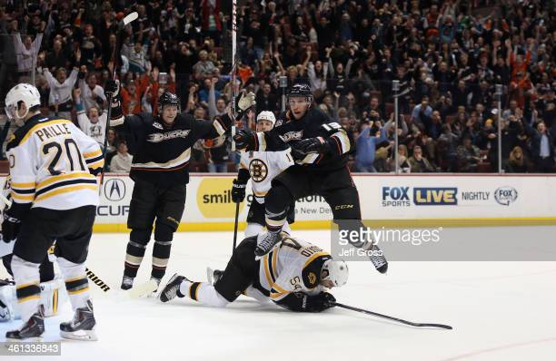 Nick Bonino of the Anaheim Ducks leaps over Adam McQuaid of the Boston Bruins after scoring a goal as Corey Perry of the Ducks celebrates in the...